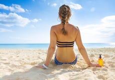 泳装的晒日光浴健康的妇女在海滨 免版税库存照片