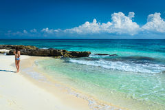 泳装的美丽的女孩在热带海滩的海 年轻wom 免版税库存图片