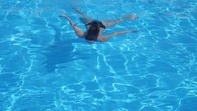泳装的美丽的女性浮动在蓝色清楚的水下在游泳池边入暑假 股票视频