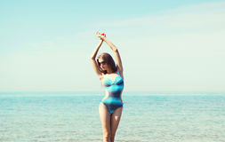 泳装的美丽的妇女反对海 库存照片