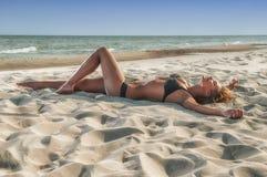 泳装的美丽的妇女在海滩 免版税图库摄影