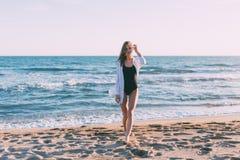 泳装的美丽的少妇在海滩 免版税库存图片