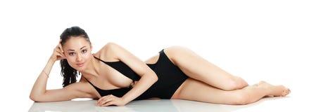 黑泳装的美丽的微笑的妇女是 库存图片