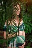 泳装的美丽的怀孕的白种人红头发人妇女在棕榈l 库存照片