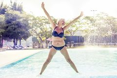 泳装的美丽的成熟妇女做体操 免版税库存图片