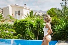 泳装的美丽,性感和时兴的白肤金发的式样女孩有摆在游泳池的运动的形状的 免版税库存照片