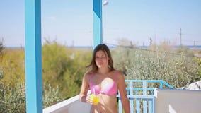 泳装的苗条夫人沿在城市之外的夏天大阳台去 股票录像