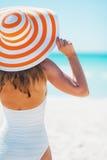 泳装调查距离的海滩帽子的少妇 免版税库存图片