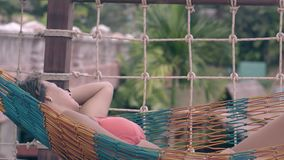 泳装谎言的亭亭玉立的女孩在镶边吊床和睡眠 影视素材