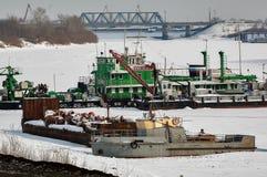 泵浦挖泥机和小船在冬天停车处 免版税库存照片
