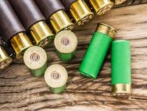 泵浦猎枪的12个测量仪弹药筒在桌上 免版税库存图片