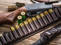 泵浦行为猎枪, 12测量弹药筒和猎刀 免版税库存图片