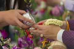 泼水节-倾倒水和花在前辈的手的之上青年人Songkran仪式的 免版税库存照片