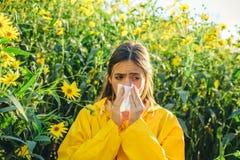 洋姜开花 鼻涕的餐巾 穿救生服的妇女 花粉过敏,打喷嚏在a的女孩 免版税库存照片