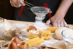洒准备面团的面粉厨师,烹调新意大利未煮过的自创面团tagliatelle在木桌上,在t的手上 免版税库存图片