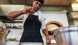 洒在盘的厨师香料在商业厨房里 免版税图库摄影