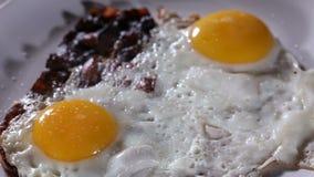 洒海盐和地面黑胡椒在煎蛋和烟肉 股票视频