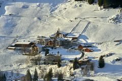洒满阳光的小山倾斜的在晴朗的冬天下午, Ischgl蒂罗尔阿尔卑斯积雪的山村 图库摄影
