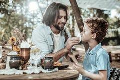 洗他的儿子面孔的宜人的有胡子的父亲 免版税库存照片