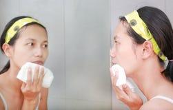洗她的与毛巾的妇女清洁面孔反射与卫生间镜子 免版税库存图片