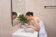 洗她的在水槽的亚裔少妇面孔 免版税库存照片