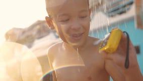 洗海滩澡和观看在防水照相机的孩子照片 股票录像