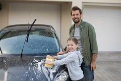 洗涤一辆汽车的十几岁的女孩和父亲在一个晴天 库存照片