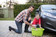洗涤一辆汽车的十几岁的女孩和父亲在一个晴天 免版税库存照片