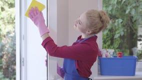 洗涤与窗口旧布的蓝色围裙的俏丽的微笑的白肤金发的女孩窗口在屋子里 清洗的天 ? 影视素材