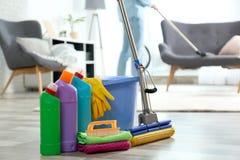 洗涤剂、桶和拖把在地板上与管理员吸尘的地毯 免版税库存图片