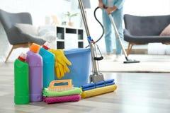 洗涤剂、桶和拖把在地板上与管理员吸尘的地毯 库存照片