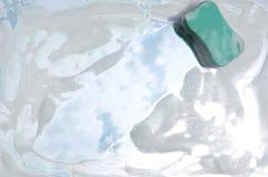 洗涤剂泡沫和擦洗用的厚垫在镜子,反射了天空 免版税图库摄影