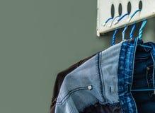 洗涤和垂悬在挂衣架的牛仔裤 库存图片