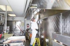 洗涤在水槽的商业厨房工作者在专业厨房里 免版税库存图片