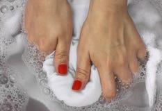 洗涤在水池的女性手白色衣裳 免版税库存照片