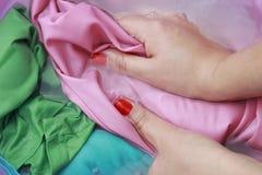 洗涤在水池的女性手颜色衣裳 免版税库存照片