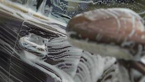 洗涤有泡沫似的海绵的,司机的男性手豪华汽车照料车 影视素材