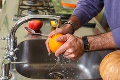 洗涤桔子用从轻拍的水 库存图片