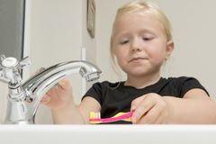 洗涤牙刷的小女孩在卫生间水槽 免版税库存图片