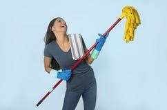 洗涤的手套的年轻可爱的愉快的拉丁妇女拿着拖把获得乐趣唱和演奏Air Guitar的激发 免版税库存图片