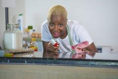 洗涤的橡胶的年轻美丽和愉快的美国黑人的黑人妇女给有布料微笑的快乐的清洁家庭厨房穿衣 免版税库存照片