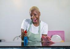 洗涤的橡胶的年轻美丽和愉快的美国黑人的黑人妇女给有布料微笑的快乐的清洁家庭厨房穿衣 库存图片