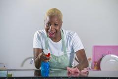 洗涤的橡胶的年轻美丽和愉快的非裔美国人的黑人妇女给有布料微笑的清洁家庭厨房穿衣快乐 免版税库存照片