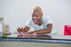洗涤的橡胶的年轻美丽和愉快的非裔美国人的黑人妇女给有布料微笑的清洁家庭厨房穿衣快乐 免版税图库摄影