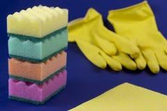 洗涤的海绵和在国内蓝色的背景的黄色手套 免版税库存照片