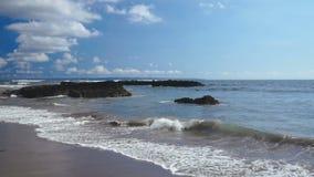 洗涤黑暗的沙子的泡沫似的海浪靠岸与岩石 股票视频