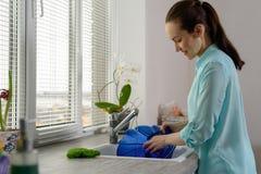 洗碗盘行为 有蓝色板材的少妇在厨房窗口前面 免版税库存照片