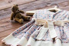洗礼仪式婴孩` s礼服垂悬在挂衣架的-选择聚焦,拷贝空间 库存照片