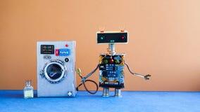 洗衣机洗衣店概念 机器人在内部棕色的墙壁,蓝色地板上的房子大师 滑稽的玩具创造性的设计 库存图片