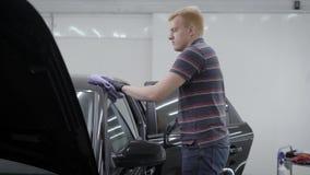 洗衣机由软的布料抹被清洗的黑汽车在洗涤,擦亮以后它在汽车车间里屋子  股票视频